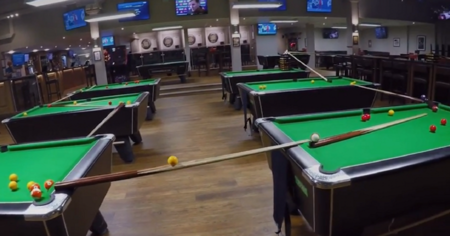 This pool trick shot is so good it needed nine tables and a golf club to complete