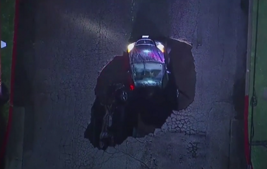 This dramatic footage shows two cars being swallowed up by a huge sinkhole in LA