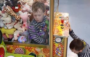 Boy grabs prizes by climbing inside claw machine