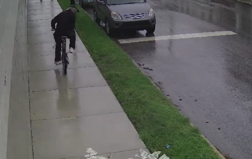 Watch: Clumsy robbery suspect drops stacks of cash from his pushbike