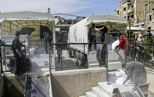 Thousands flee besieged enclave in Syria as aid convoy arrives