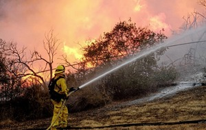 Intentionally set wildfire gets perilously close to homes in southern California