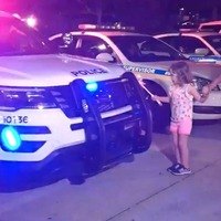 Watch this cute kid lighting up police cars by 'magic'