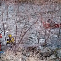 Emergency workers removing car from icy river find man alive inside