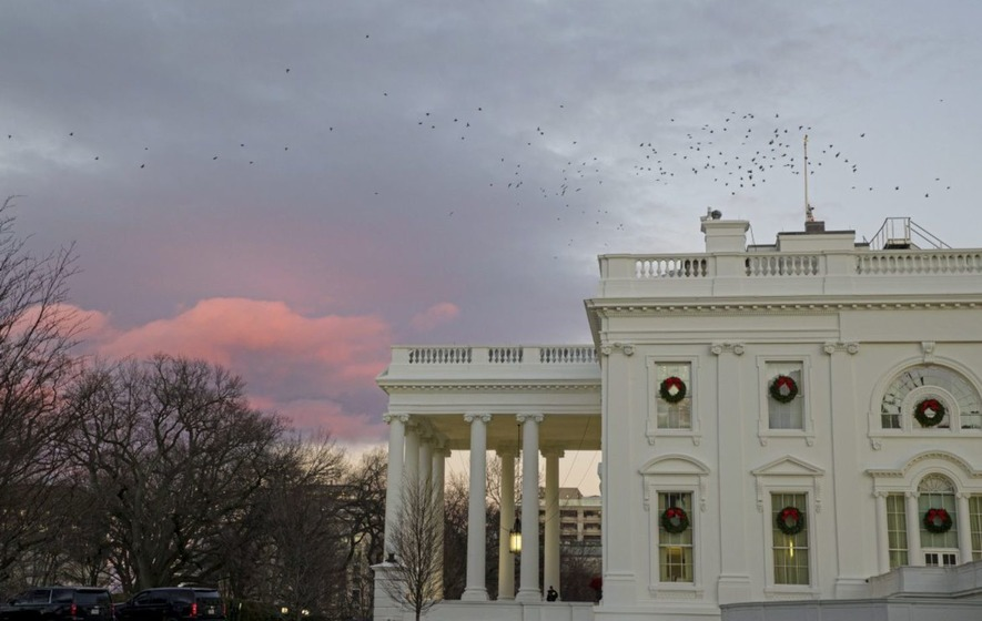 The setting sun illuminates clouds behind the White House during a partial federal shutdown