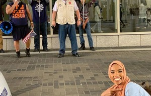 Woman wearing hijab takes smiling picture in front of anti-Islam protesters