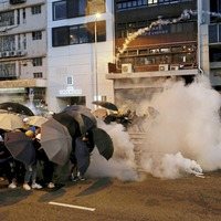 Police fire tear gas as Hong Kong protesters block roads