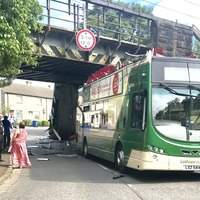 Driver charged after bus roof ripped off in railway bridge crash