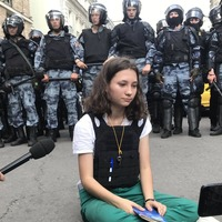 Viral photo shows teenage girl reading Russian constitution to riot police