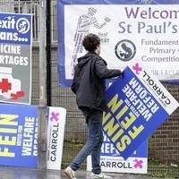 People Before Profit hang anti-Sinn Féin posters in west Belfast