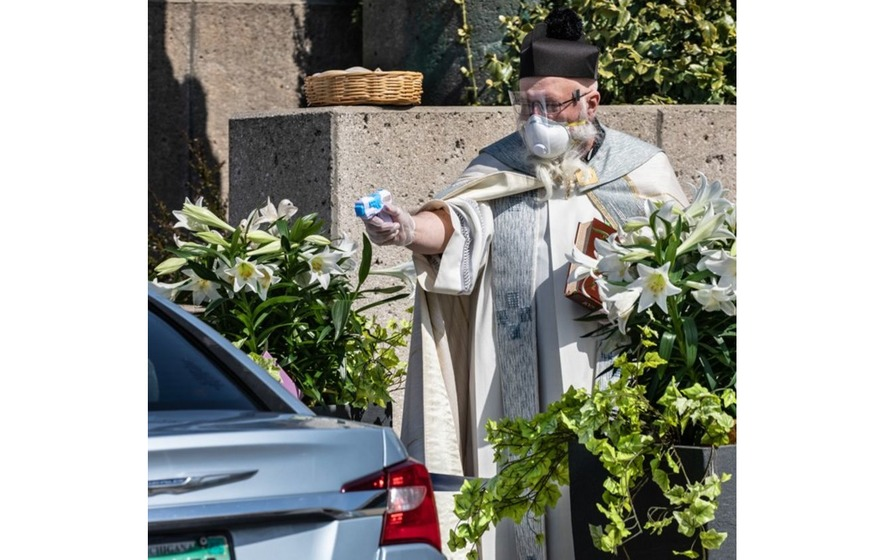 Priest blessing parishioners with water pistol