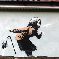 Banksy-style artwork of sneezing woman appears on wall