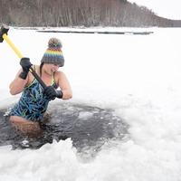 Outdoor swimmer uses sledgehammer to break up ice on frozen loch