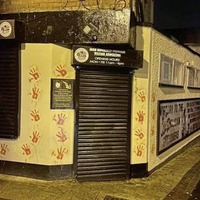 Friends of Lyra McKee daub red hand signs on dissident HQ