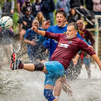 Annual river football clash goes ahead despite waterlogged pitch